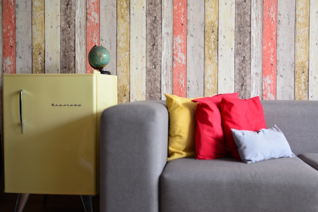 Beautiful room decor with a globe and a yellow retro fridge.