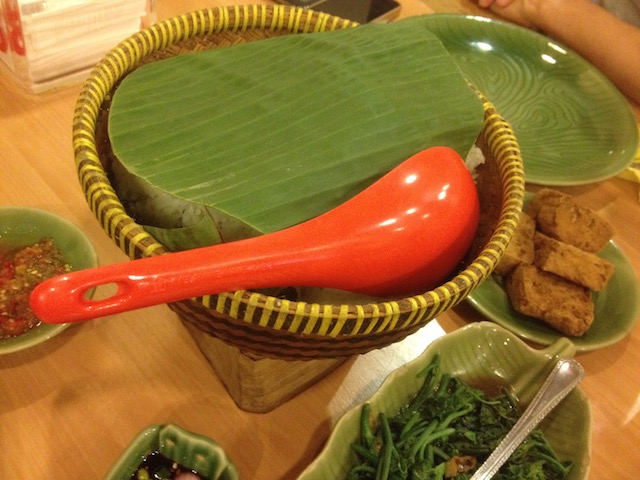 White rice served in a basket covered with a cut banana leaf